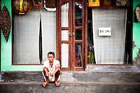 "Man sits on a sidewalk with bare feet in front of a small shop in Bali, Indonesia.  The shop announces a ""Big Sale"" with a small simple sign hung in the window."