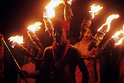 Sri Lanka. Participant at the annual festival at the pilgrim site, Kataragama. He wears a fan of flaming torches that look like a peacock's tale. the peacock is the vehicle of Lord Murugan, or Skanda, the God of Kataragama.