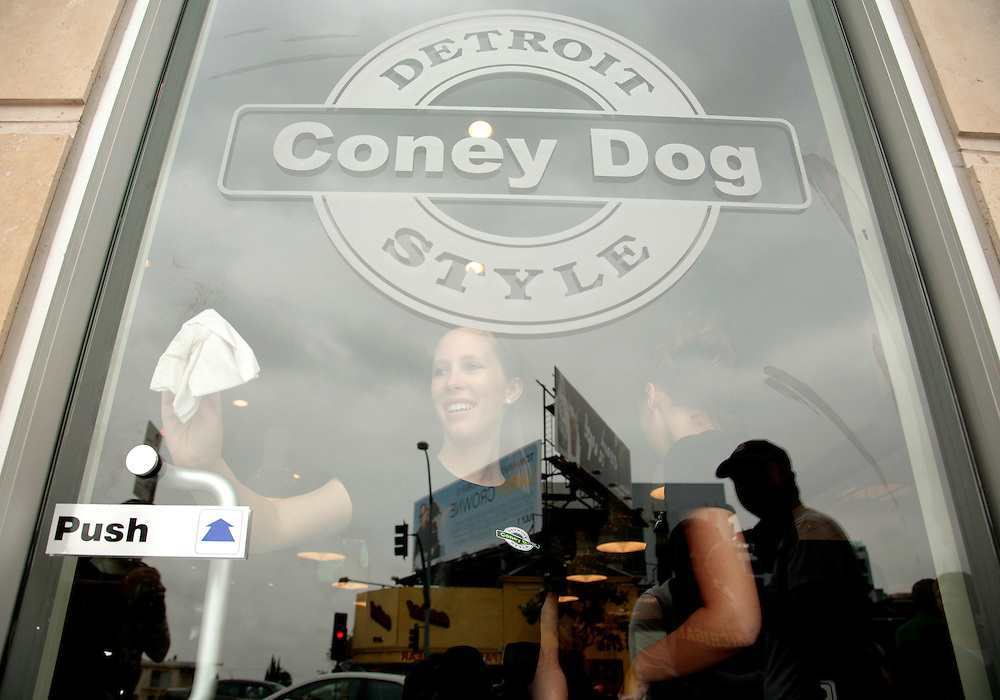 Employee Olivia Whitehead cleans windows before the opening of Coney Dog, a Detroit-style Coney Island hot dog restaurant, on Sunset Boulevard in West Hollywood, Calif., Saturday, June 19, 2011. (AP Photo/Jason Redmond)