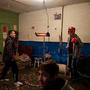 A group of young men inside an improvised bomb shelter in the basement of a residential building in central Donetsk.