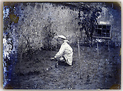 young boy in white sailor suite tending to his garden Paris 1900s