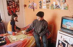 Teenage boy and girl playing board game in bedroom,