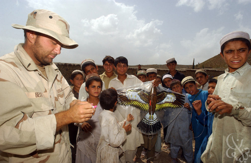 A U.S. Civil Affairs soldier hands out kites to Afghan children during a joint US-UK humanitarian mission June 18, 2002 in southeastern Afghanistan.