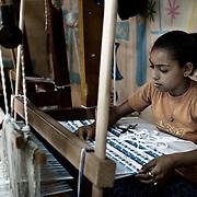 """Una niña aprende a tejer alfombras en el taller de la ONG, A.P.E. en Mokattam, donde utilizan materiales reciclados provenientes de fábricas de ropa y telas de todo Egipto. En medio del barrio de Manshiet Nasr a las afueras de El Cairo esta situado el asentamiento de Mokattam conocido como la """"Ciudad de la Basura"""" , está habitado por los Zabbaleen ,una comunidad de unos 45.000 cristianos coptos que viven desde hace varias décadas de reciclar los desperdicios que genera la capital egipcia: plástico, aluminio, papel y desechos órganicos que transforman en compost . La mayoría forman parte de la Asociación para la Protección del Ambiente (APE) una ONG que actúa en el área, cuyos objetivos son proteger el medio ambiente y aumentar el sustento de las recuperadores de basura de El Cairo. Según la ONU, el trabajo que se realiza en Mokattam como uno de los diez mejores ejemplos del mundo en el mejoramiento medioambiental. El Cairo , Egipto, Junio 2011. ( Foto : Jordi Camí )"""