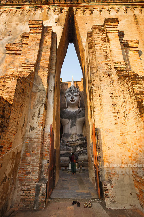 What si chum, Sukhothai, Thailand - the colossal Buddha statue peers through the narrow opening of the wat