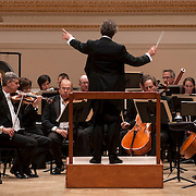 """November 13, 2012 - New York, NY : Music director and conductor Franz Welser-Möst (at podium) leads The Cleveland Orchestra, featuring trumpeters Michael Sachs (standing at left) and Jack Sutte (standing at right) in the New York premiere of Matthias Pintscher's """"Chute d'Étoiles"""" (2012) at Carnegie Hall's Isaac Stern Auditorium / Ronald O. Perelman Stage on Tuesday evening. CREDIT: Karsten Moran for The New York Times"""
