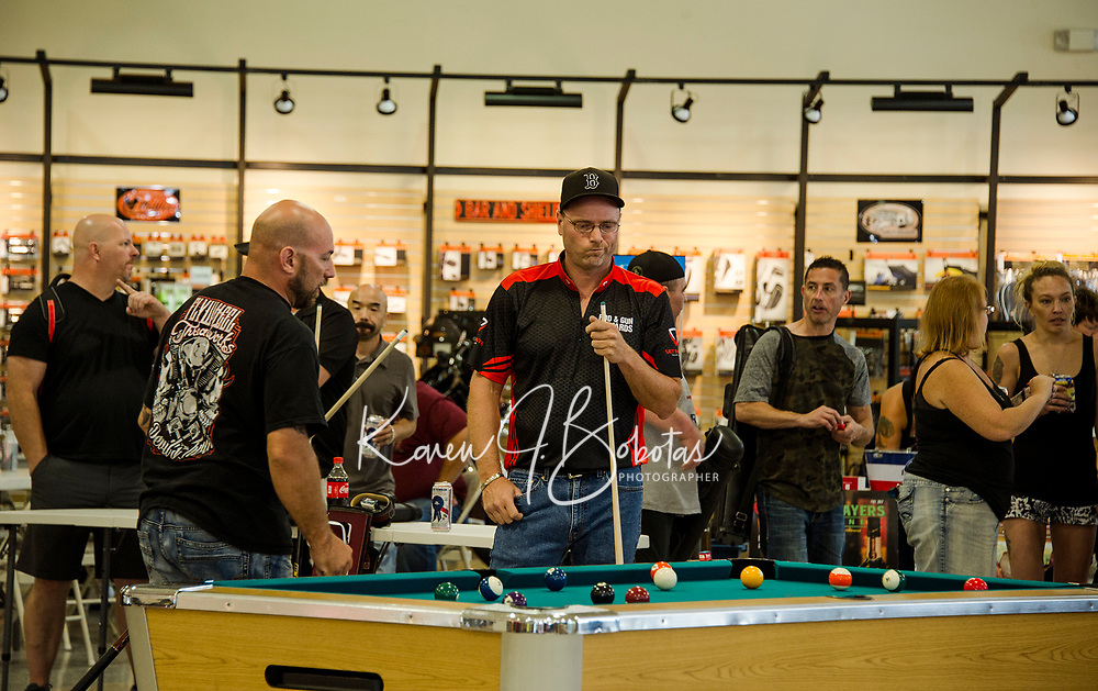 Bill Pliakos and Scott Hooper contemplate their next shot during the Harley Davidson Pool Tournament with Tavern Players on Sunday afternoon at Laconia Harley.  (Karen Bobotas/for the Laconia Daily Sun)