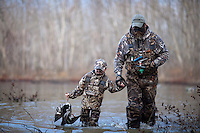 DUCK HUNTER AND A YOUNG BOY WEARING REALTREE MAX 4 CAMOUFLAGE WADING THROUGH THE WATER AFTER RETRIEVING A DOWNED DUCK