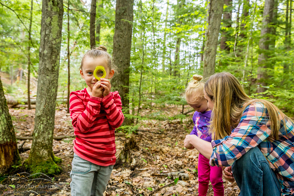 A woman plays with two young girls in the woods at the Orris Falls Preserve in South Berwick, Maine.