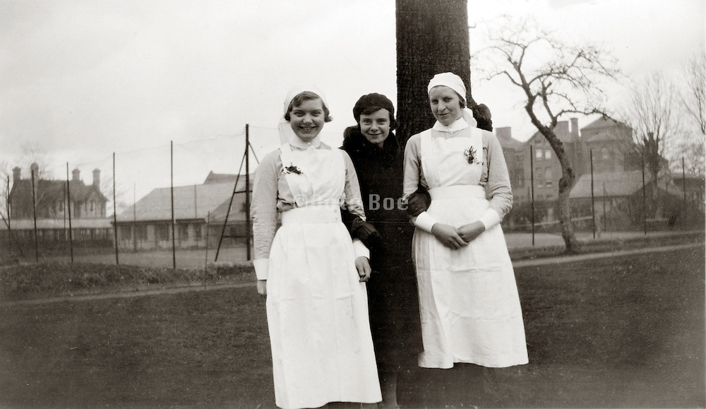 two young adult nurses posing with colleague in civil clothing England 1930s