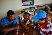 A group of migrants plays a board game with an improvised board and chips in the Casa del Migrante in Arriaga, Mexico, April 17, 2013.