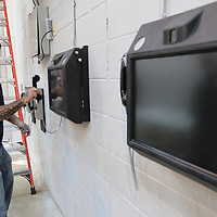 Paul Landry, an installer with City Tele Coin in Bossier City, Louisiana, places the phone receiver on the hook of one of two monitor systems he installed inside the A Pod cell at the Lee County Jail on Tuesday.