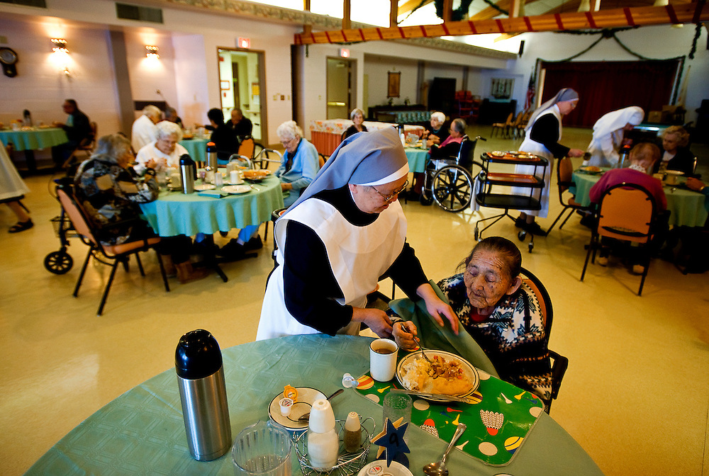 121608     Brian Leddy.Sister Christine *(didn't want to give her last name)* helps hope Davis with her lunch at Little Sisters of the Poor on Tuesday. The organization will soon celebrate it's 25th anniversary.