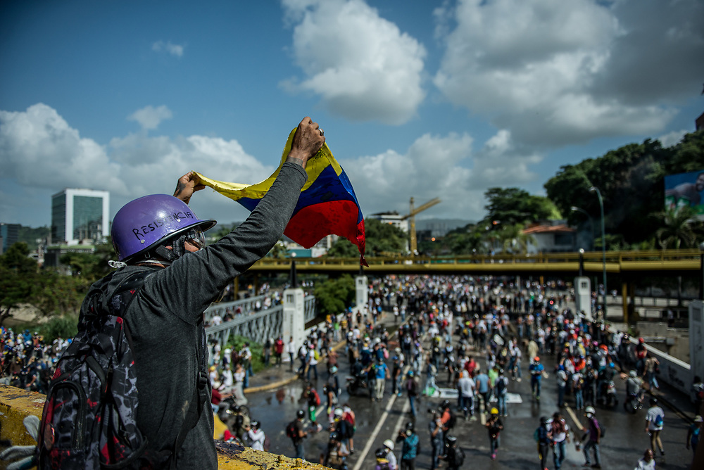 CARACAS, VENEZUELA - MAY 26, 2017:  An anti-government protester celebrates, and waves a small flag of Venezuela from a highway overpass, after protesters successfully fought to take the stragetic overpass from National Guard soldiers. The streets of Caracas and other cities across Venezuela have been filled with tens of thousands of demonstrators for nearly 100 days of massive protests, held since April 1st. Protesters are enraged at the government for becoming an increasingly repressive, authoritarian regime that has delayed elections, used armed government loyalist to threaten dissidents, called for the Constitution to be re-written to favor them, jailed and tortured protesters and members of the political opposition, and whose corruption and failed economic policy has caused the current economic crisis that has led to widespread food and medicine shortages across the country.  Independent local media report nearly 100 people have been killed during protests and protest-related riots and looting.  The government currently only officially reports 75 deaths.  Over 2,000 people have been injured, and over 3,000 protesters have been detained by authorities.  PHOTO: Meridith Kohut