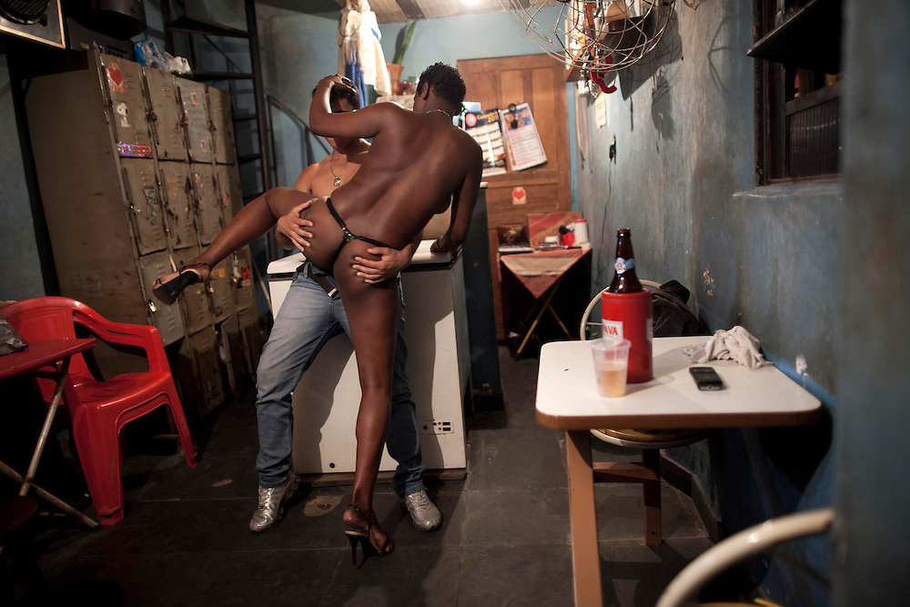 In this photo taken May 5, 2011, a sex worker dances with a customer at the Vila Mimosa prostitution zone in Rio de Janeiro, Brazil. <br /> <br /> Spelling the possible end of Vila Mimosa is a high-speed train the government wants to build to link Rio to Sao Paulo, as part of Brazil's Olympic proposal. The government is expected to open bidding to prospective builders July 29.