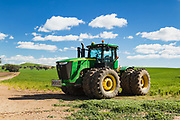 John Deere 9410R four-wheel drive (4WD) tractor in farm pasture paddock under cumulus cloud near  Woodstock, New South Wales, Australia. <br />