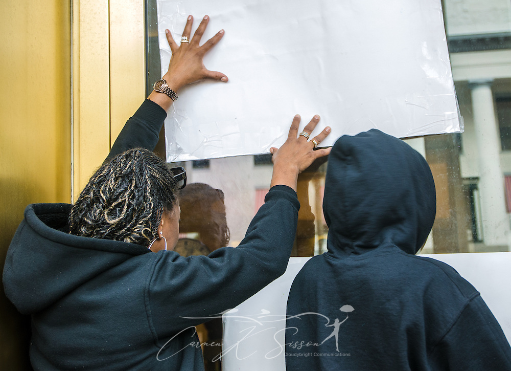 """Denise Demps-Knight, 43, holds up a poster as she and Kennedy Jones, 13, stand with protestors outside the Florida Capitol Complex executive tower on July 20, 2013, chanting support for members of Dream Defenders, a youth-led activist group which sequestered itself within the building July 16, demanding a special legislative session to address concerns over racial profiling and Florida's """"stand-your-ground"""" self-defense law. The group formed in 2012 after the fatal shooting of 17-year-old Trayvon Martin.  (Photo by Carmen K. Sisson/Cloudybright)"""