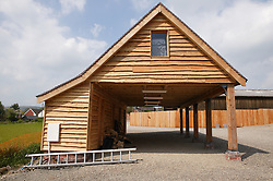Wooden car port incorporating storage space at Eco House at The Wintles; Bishop's Castle,