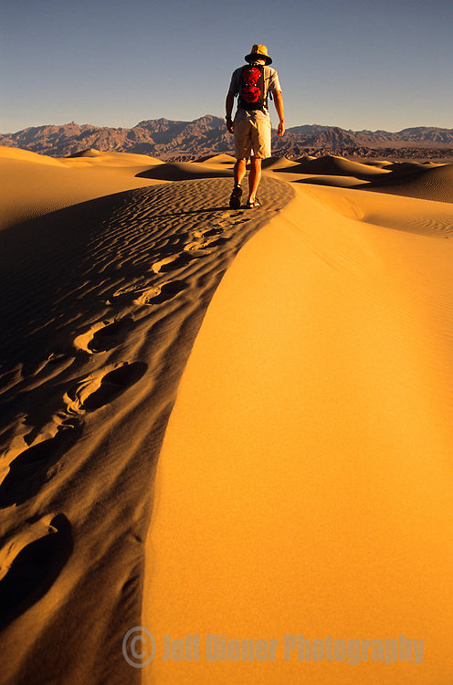 A young man hikes along the Stovepipe Wells sand dunes in Death Valley National Park, California.