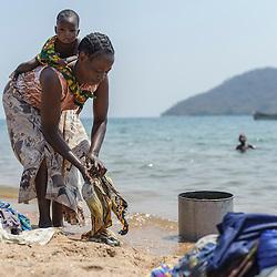Woman washing clothes on the shore of Lake Malawi, Malawi, Africa
