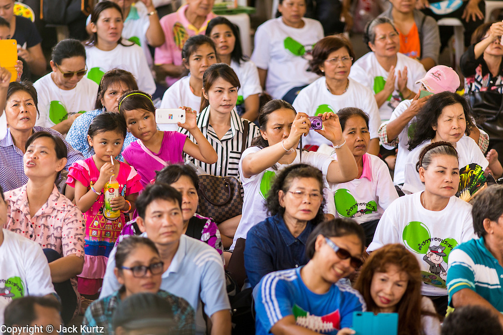 """15 JUNE 2014 - BANGKOK, THAILAND:  People watch a police band perform in Lumpini Park in Bangkok. The Thai military junta, formally called the National Council for Peace and Order (NCPO), is sponsoring a series of events throughout Thailand to restore """"Happiness to Thais."""" The events feature live music, dancing girls, military and police choirs, health screenings and free food.  PHOTO BY JACK KURTZ"""