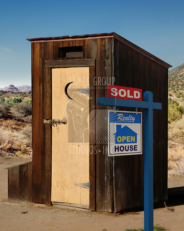 A realestate sign showing a dumppy out-house sold in the desert.