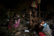 Ja smokes in the cave that his family moved in to until the monsoon rains subside.<br /> <br /> Evidence suggests that the Maniq, a Negrito tribe of hunters and gatherers, have inhabited the Malay Peninsula for around 25,000 years. Today a population of approximately 350 maniq remain, marooned on a forest covered mountain range in Southern Thailand. Whilst some have left their traditional life forming small villages, the majority still live the way they have for millennia, moving around the forest following food sources. <br /> <br /> Quiet and reclusive they are little known even in Thailand itself but due to rapid deforestation they are finding it harder to survive on the forest alone and are slowly being forced to move to its peripheries closer to Thai communities.