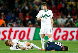 Nejc Pecnik of Slovenia injured by Clint Dempsey of USA (R), Bostjan Cesar of Slovenia (C) during the 2010 FIFA World Cup South Africa Group C match between Slovenia and USA at Ellis Park Stadium on June 18, 2010 in Johannesberg, South Africa. (Photo by Vid Ponikvar / Sportida)