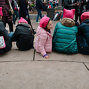 A little girl look on at the continuing flow of people during the Women's March on Washington, D.C., January 21, 2017