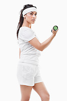 Portrait of young Asian woman raising dumbbell over white background