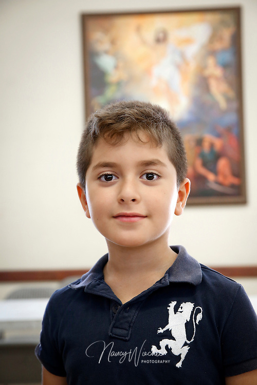 Nine-year-old Saif Alosh poses in front of an image of the Risen Christ at St. Michael Chaldean Catholic Church in El Cajon, Calif., Aug. 14, 2015.  (Nancy Wiechec for ONE magazine)
