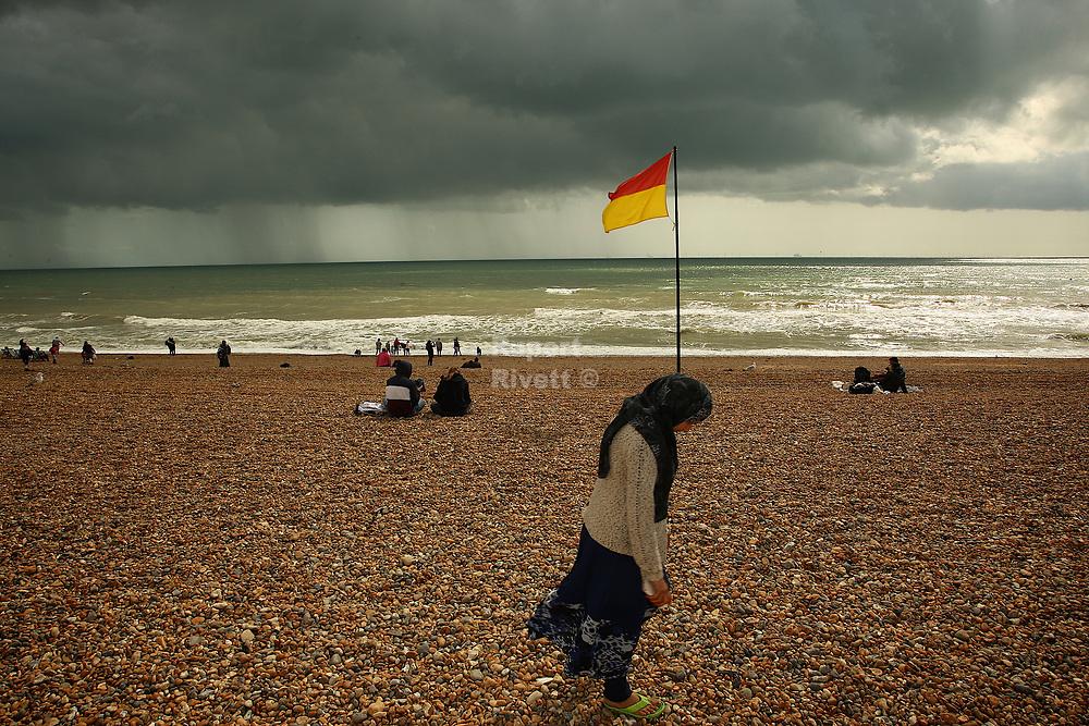 Lady wearing a flag walks along Brighton Beach
