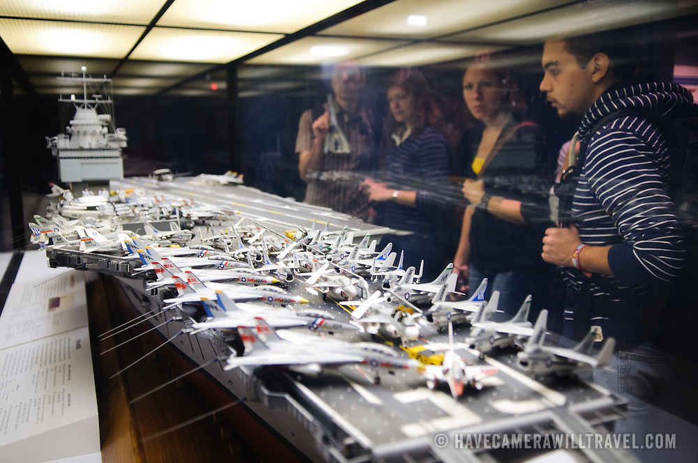 Visitors to the National Air and Space Museum look at a detailed model of the USS Enterprise aircraft carrier