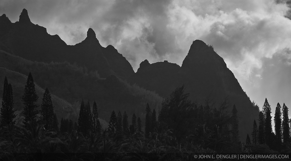 The dramatic peaks of Makana Ridge above Haena and Kee Beach mark the begining of the Na Pali coast on the Island of Kauai in Hawaii. The main peak, Makana (right), was used by early Hawaiians to conduct the fire throwing ceremony called oahi. On special occasions firethrowers climbed the cliffs to the top of Makana with logs that were set  on fire at night and thrown out over the ocean. Updrafts kept the logs and sparks aloft for up to a mile out to sea in a dramatic display. In more recent times, the peak has been associated with the movie South Pacific where the peak represented Bali Hai.