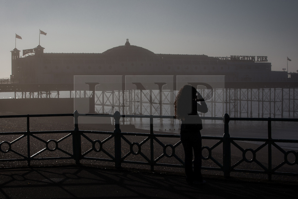 © Licensed to London News Pictures . 24/09/2013 . Brighton , UK . A woman stares out through hazy sunshine above the Brighton seafront landscape this morning (Tuesday 24th September 2013) towards Brighton Pier. Photo credit : Joel Goodman/LNP