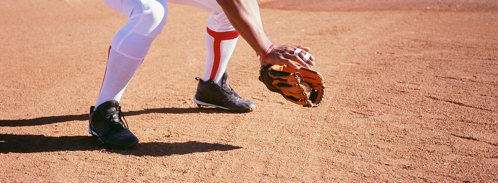 Low section of baseball catcher in position on field