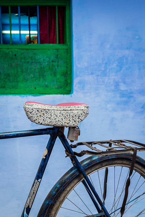 Detail of a bike standing against an indigo wall.