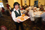 A server showcases dessert plates at Great Mall Mayflower Restaurant in Milpitas, California, on September 11, 2014. (Stan Olszewski/SOSKIphoto)