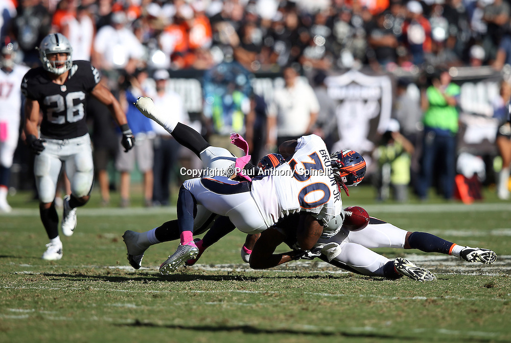 Oakland Raiders tight end Mychal Rivera (81) fumbles the ball on a fourth quarter pass reception as he gets gang tackled by Denver Broncos strong safety David Bruton, Jr. (30) and a Broncos teammate during the 2015 NFL week 5 regular season football game against the Denver Broncos on Sunday, Oct. 11, 2015 in Oakland, Calif. The fumble was recovered by the Broncos. The Broncos won the game 16-10. (©Paul Anthony Spinelli)