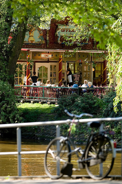 Tourists relax and enjoy a break at a canal side cafe in Amsterdam.