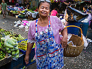 "12 JANUARY 2016 - BANGKOK, THAILAND: A shopper in Khlong Toey Market in Bangkok. Khlong Toey (also called Khlong Toei) Market is one of the largest ""wet markets"" in Thailand. The market is located in the midst of one of Bangkok's largest slum areas and close to the city's original deep water port. Thousands of people live in the neighboring slum area. Thousands more shop in the sprawling market for fresh fruits and vegetables as well meat, fish and poultry.         PHOTO BY JACK KURTZ"