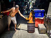 "05 SEPTEMBER 2017 - BANGKOK, THAILAND:  A man in Bangkok's Chinatown burns ghost money on Hungry Ghost Day. The Ghost Festival is a Buddhist and Taoist holy day celebrated on the 15th day of the 7th lunar month. It is primarily celebrated in China and Chinese communities outisde China. In Thailand, it's celebrated in Thai-Chinese communities in Bangkok, Phuket and Chiang Mai.  On that day ghosts and spirits, including those of the deceased ancestors, come out from the lower realm to visit the living. Families prepare elaborate banquets for the spirits and burn ""ghost money"" for the spirits to use in the other realm. It is a day for venerating dead relatives.     PHOTO BY JACK KURTZ"