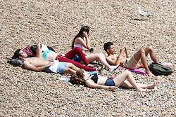 © Licensed to London News Pictures. 24/06/2015. Brighton, UK. Hundreds of people take advantage of the afternoon sunshine to relax and sunbathe on Brighton beach, today June 24th 2015. Photo credit : Hugo Michiels/LNP