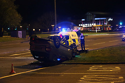 Reading,Berkshire Friday 31st March 2017 A driver has walked away to tell the tail after leaving a trail of destruction on the A329 in Winnersh Berkshire this evening just outside the Showcase Cinema.This is the aftermath of the  moment a car flips in the middle of the road after hitting a traffic light - then slides along carriageway on its roof.<br /> <br /> The incident happened on the A329 Reading Road outside the cinema.  One shocked film goers described hearing a loud bang and the car flying through the air at speed. <br /> The vehicle collides head on with a traffic island, sending debris flying, and is lifted onto two wheels. The car swerves out of control  to other side of the road lands on its roof, and comes to a halt amid a shower of sparks.<br /> <br /> The silver  A3 driver has left thousand of pounds worth of damage to the traffic island barriers and traffic lights.  <br /> Emergency services rushed to the scene just before midnight on Thursday evening. Fire crews from near by Wokingham Road made the vehicle safe whilst Police took the driver away for questioning. A major clean up operation is now taking place to make the road ready for the morning rush hour traffic&copy;UKNIP