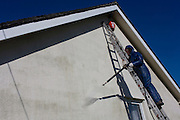 A middle-aged man power washes the white render on the exterior of his bungalow home.