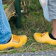Nederland Giessen  26 augustus 2009 200900826 ..Serie levensmiddelensector. Close up klompen van vader en zoon, gewoontes, tradities, generaties, beivloeden.  Closeup, wooden shoes of father and son in rural area. ..Foto: David Rozing