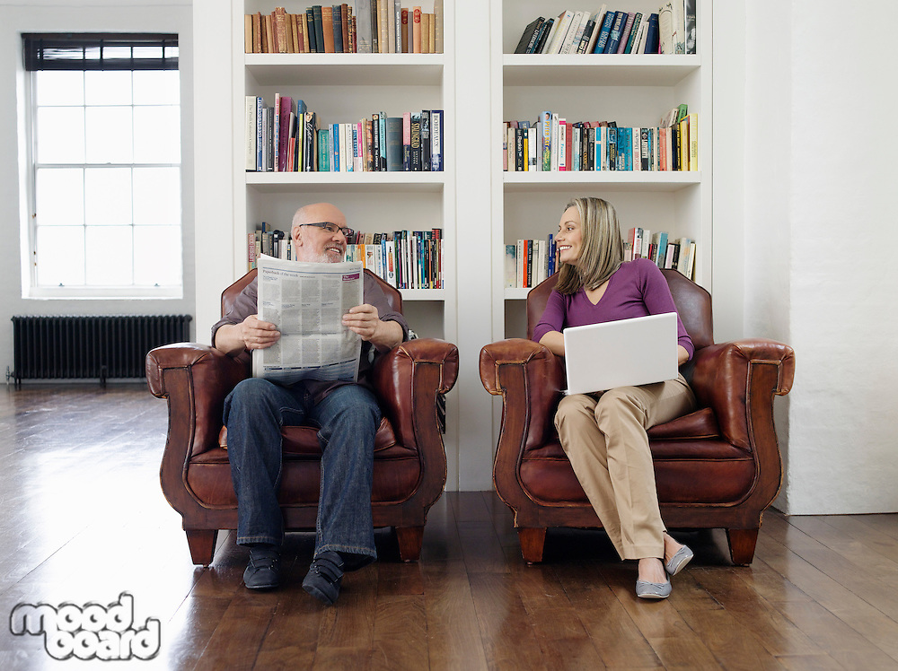 Couple sitting in armchairs man reading newspaper woman using laptop