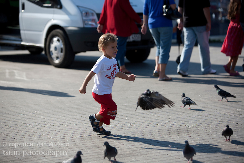 A boy running through pigeons flocked on the group in Taksim Square