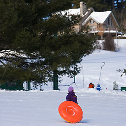 A young girl (age 6) climbs a sledding hill in Quechee, Vermont.