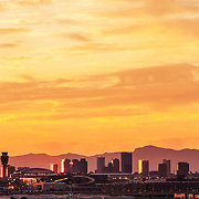 Planes fly into Phoenix Sky Harbor International Airport at dusk with downtown Phoenix in the background.